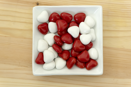 Delicious red and white chocolate dragees on white plate over wooden background. Reklamní fotografie
