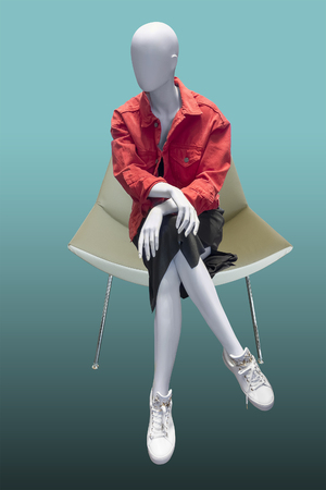 Sitting female mannequin wearing red jacket and black skirt, isolated.  No brand names or copyright objects.