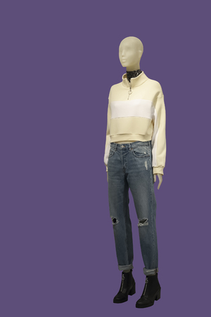 Full-length female mannequin wearing yellow jumper and blue ripped jeans, isolated. No brand names or copyright objects.