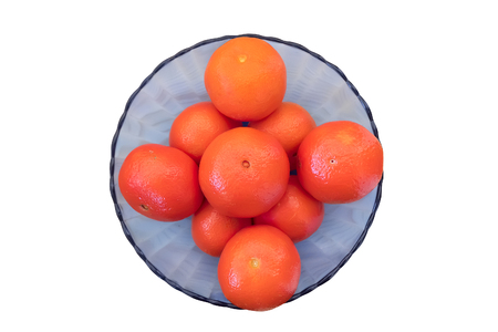 Ripe mandarins in blue glass bowl isolated on white background.  Top view.