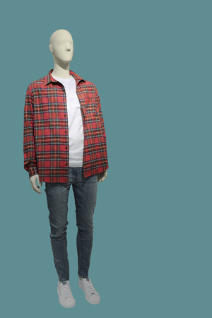 Full-length male mannequin dressed in red plaid shirt and blue jeans, isolated. No brand names or copyright objects.