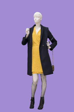 Full-length female mannequin wearing black coat and yellow dress.  Isolated. No brand names or copyright objects.