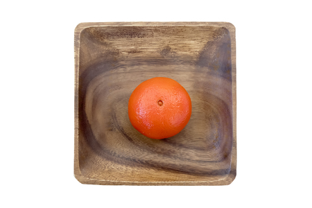 Single mandarin in a wooden bowl. Top view. Isolated on white background.