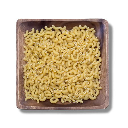 Uncooked pasta on wooden square plate. Isolated on white background. Reklamní fotografie