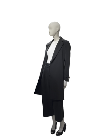 Full-length female mannequin wearing black coat and skirt trousers.  Isolated on white background. No brand names or copyright objects.