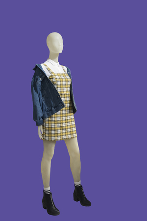 Full-length female mannequin dressed in blue jeans jacket and yellow plaid sundress, isolated. No brand names or copyright objects.