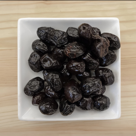 Smoked black olives in plate over wood background. Top view.
