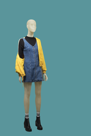 Full-length female mannequin dressed in yellow jacket and blue jeans sundress, isolated on green background. No brand names or copyright objects.