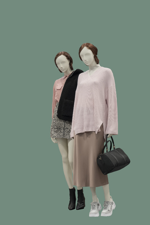 Two full-length female mannequins dressed in fashionable clothes, isolated on green background. No brand names or copyright objects.