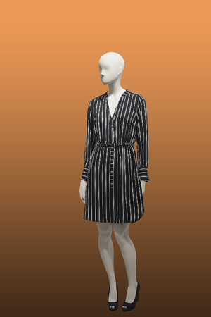 Full-length female mannequin wearing black striped dress, isolated. No brand names or copyright objects. Reklamní fotografie