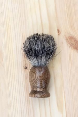 Hand-made badger shaving brush on wooden background. Reklamní fotografie