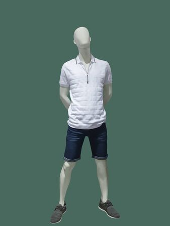 Full-length male mannequin dressed in casual clothes over green background. No brand names or copyright objects.