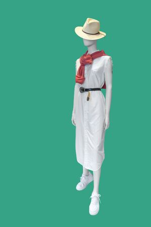 Full-length female mannequin wearing fashionable summer dress, isolated on green background. No brand names or copyright objects.