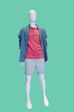 Full-length male mannequin dressed in jeans shirt and gray shorts over green background. No brand names or copyright objects.