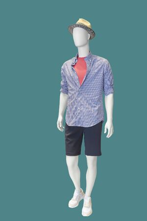 Full-length male mannequin dressed in plaid shirt and black shorts over green background. No brand names or copyright objects. Stock fotó