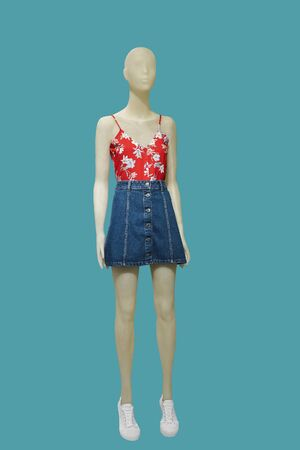 Full-length female mannequin dressed in red top and jeans skirt over green background. No brand names or copyright objects. Stock fotó