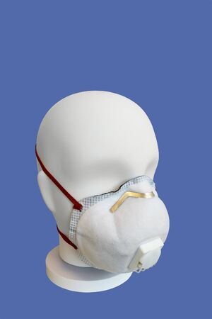 Dust mask with valve on mannequin, isolated blue background.