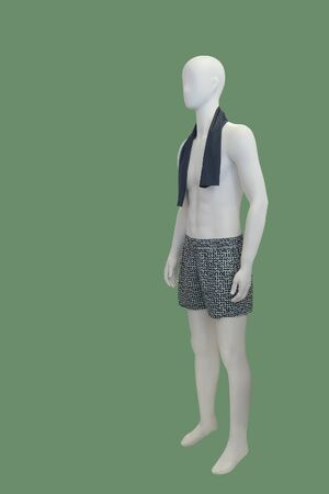 Full-length male mannequin dressed in shorts, isolated on green background.  No brand names or copyright objects.