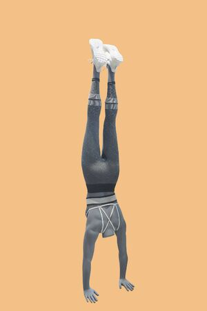 Full-length female mannequin dressed in sportswear, performing a handstand.  Isolated. No brand names or copyright objects.  Reklamní fotografie