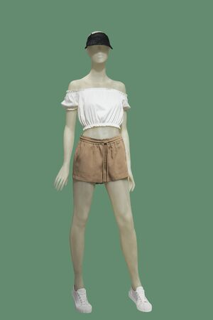 Full-length female mannequin dressed in top and shorts, isolated on white background. No brand names or copyright objects. Stock Photo
