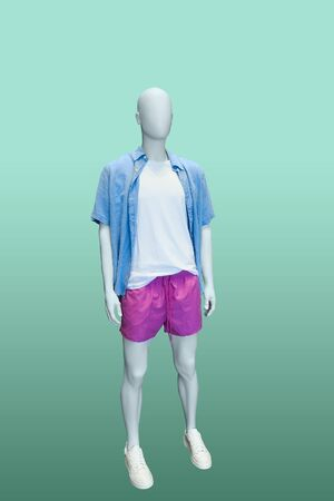 Full-length male mannequin dressed in blue short sleeve button-down shirt and red shorts, isolated on green background. No brand names or copyright objects.