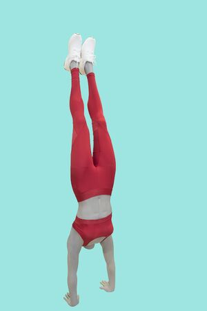 Full-length female mannequin dressed in sportswear, performing a handstand.  Isolated on a green background. No brand names or copyright objects.