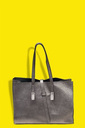 Brown leather shoulder bag over yellow background. Stok Fotoğraf