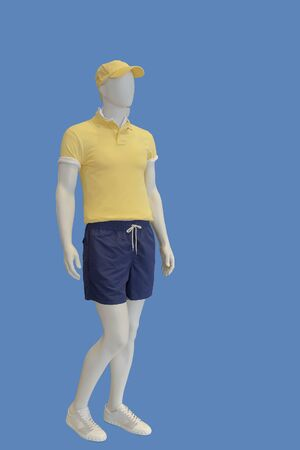 Full-length male mannequin dressed in yellow t- shirt and blue shorts, isolated on blue background. No brand names or copyright objects.