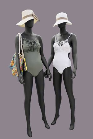 Two full-length female mannequins wearing fashionable bathing suits, isolated. No brand names or copyright objects.