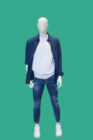 Full-length male mannequin dressed in fashionable wear, isolated on green background. No brand names or copyright objects.