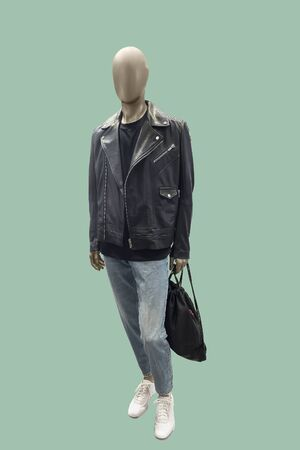 Full-lens male mannequin wearing black leather jacket and blue jeans, isolated on green background. No brand names or copyright objects.