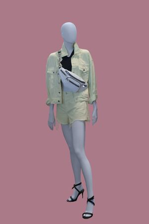 Full-length female mannequin dressed in green jeans short suit, isolated. No brand names or copyright objects.