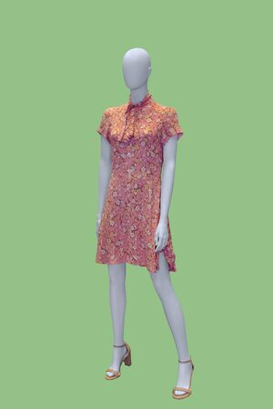 Full-length female mannequin wearing fashionable dress, isolated on green background. No brand names or copyright objects.