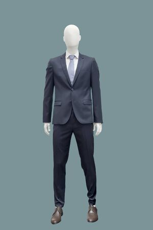 Full-length male mannequin dressed in fashionable suit, isolated on green background. No brand names or copyright objects.