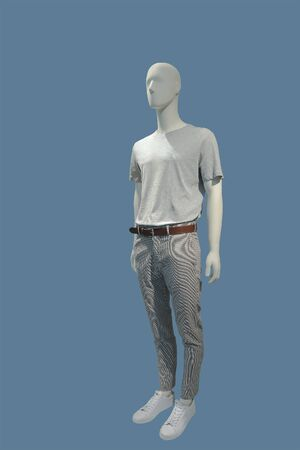 Full-length male mannequin dressed in casual clothes, isolated on blue background. No brand names or copyright objects.
