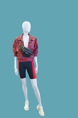 Full-length female mannequin dressed in fashionable clothes, isolated on blue background. No brand names or copyright objects. Imagens