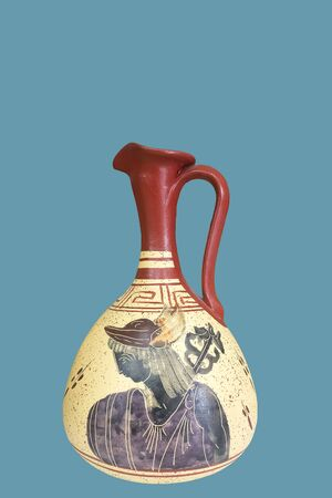 Greek-style vase. Oil cruet with painted Greek motifs. Isolated on blue background.