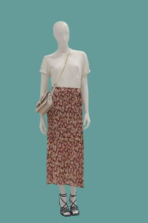 Full-length female mannequin dressed in t-shirt and skirt, isolated on green background. No brand names or copyright objects. Reklamní fotografie
