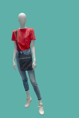 Full-length female mannequin dressed in red t-shirt and blue ripped jeans. Isolated on blue background. No brand names or copyright objects.