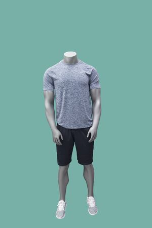 Male mannequin wearing sport athletics clothes over green background.