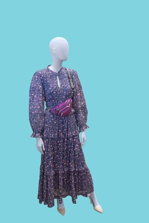 Full-length female mannequin dressed in fashionable wear. Isolated on blue background. No brand names or copyright objects.