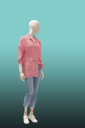 Full-length female mannequin dressed in red striped shirt and blue jeans, isolated on green background.