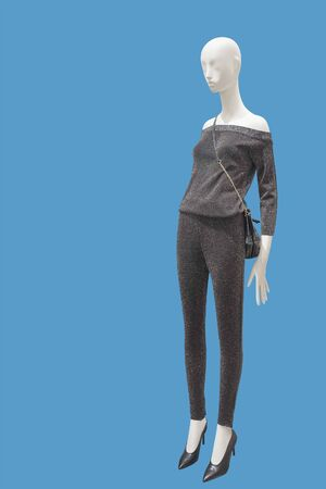 Full-length female mannequin dressed in pants suit with shoulder crop tops blouse, isolated on blue background. No brand names or copyright objects.
