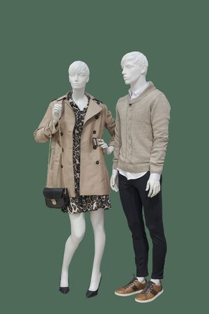 Full-length two mannequins, male and female, dressed in fashionable warm clothes, isolated on green background. No brand names or copyright objects.