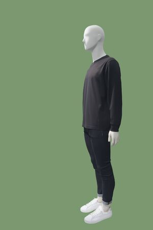 Full-length male mannequin dressed in casual clothes, isolated on green background. No brand names or copyright objects.
