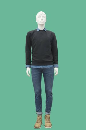 Full length male mannequin dressed in sweater and blue jeans, isolated on green background. No brand names or copyright objects.