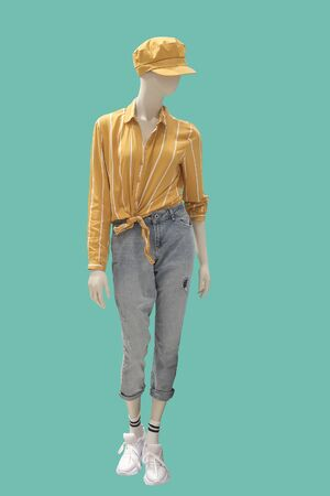 Full length female mannequin dressed in fashionable clothes, isolated on green background. No brand names or copyright objects.