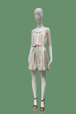 Full length female mannequin wearing white stripy short overall, isolated on green background. No brand names or copyright objects.