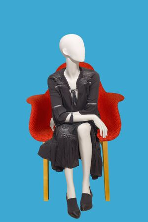 Sitting female mannequin wearing black elegant dress, isolated on blue background. No brand names or copyright objects.