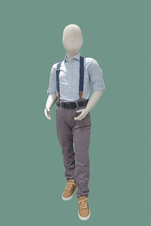 Full length child mannequin dressed in blue shirt and brown trousers, isolated on green background. No brand names or copyright objects. 版權商用圖片